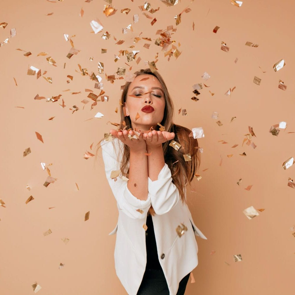 Portrait of happy lovely woman send a kiss to camera on isolated background with confetti. Happy celebration of new year, birthday