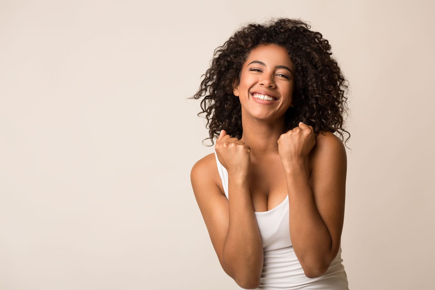 Happy pretty black girl celebrating her success on light background, copy space
